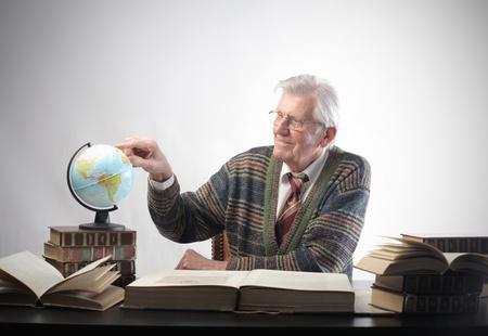 hombre estudiando: Hombre Senior estudiar geograf�a con un globo y algunos libros