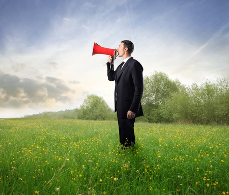 loudhailer: Businessman on a green meadow shouting in a megaphone Stock Photo