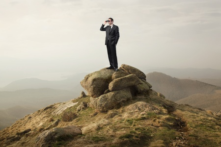 Businessman using binoculars from the top of a hill photo