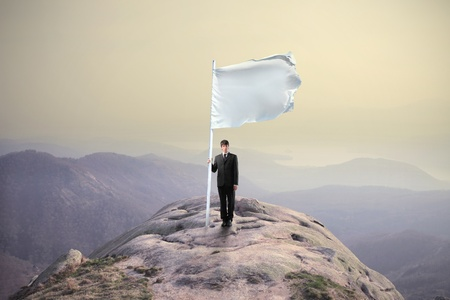 scenary: Businessman sinking a flag on the top of a mountain