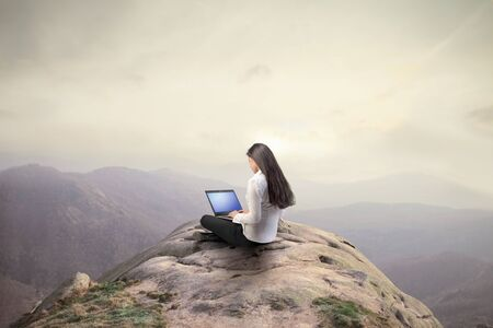 woman on top: Businesswoman using a laptop on the top of a hill
