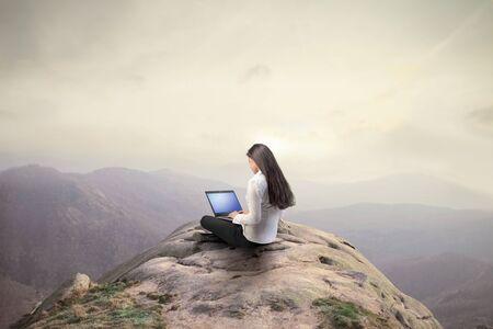 bovenaanzicht mens: Zakenvrouw met behulp van een laptop op de top van een heuvel