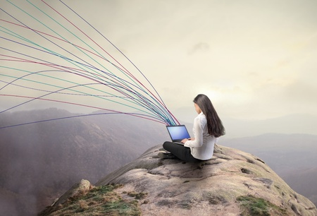 Businesswoman communicating through a laptop from a hill Stock Photo