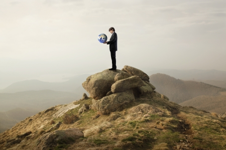 Businessman holding the Earth in his hands on a mountain
