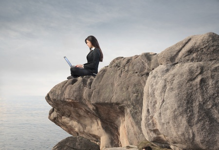 Businesswoman using a laptop from the top of a rock photo