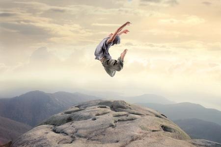 Bailarín saltando en la cima de una montaña Foto de archivo