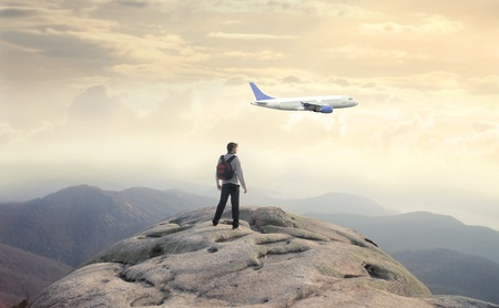 Man on the top of a mountain observing a plane photo