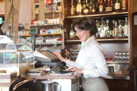 Lächelnd Kellnerin einen Gesetzentwurf in eine Bar Druck Standard-Bild