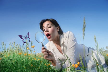 Astonished woman lying on a green meadow and observing a butterfly through a magnifying glass photo
