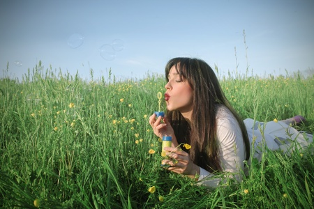 Woman lying on a green meadow and blowing soap bubbles photo
