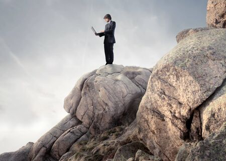 Businessman using a laptop on a rock Stock Photo - 9283549