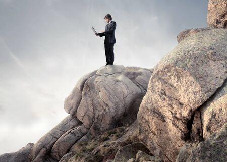 risky job: Businessman using a laptop on a rock