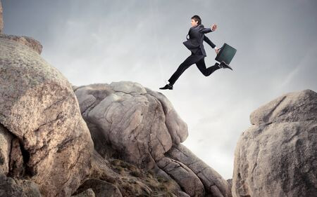 risky: Businessman jumping from a rock to another Stock Photo