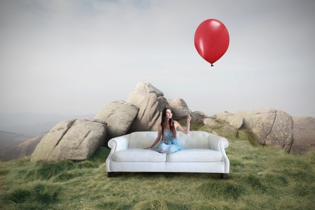 Beautiful woman sitting on a sofa on a meadow and holding a red balloon Stock Photo - 9540658