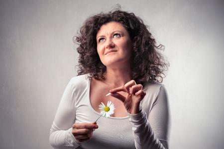 wavering: Woman wavering a daisy Stock Photo