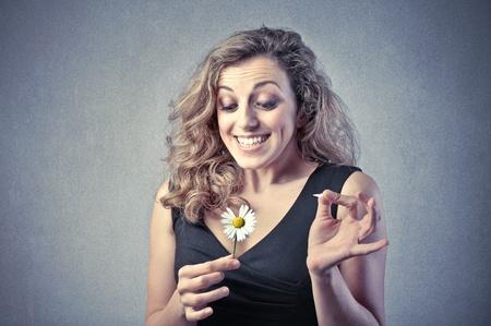wavering: Smiling beautiful woman wavering a daisy Stock Photo