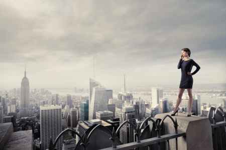 roof top: Beautiful businesswoman using a mobile phone while standing on the rooftop of a skyscraper over a city