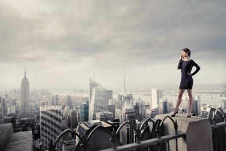 palazzo: Bella imprenditrice utilizzando un telefono cellulare, mentre in piedi sul tetto di un grattacielo in una citt� Archivio Fotografico