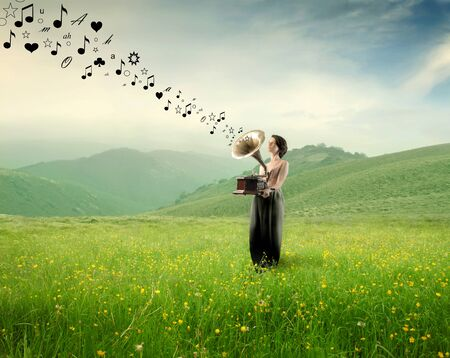 listen music: Elegant woman holding an old gramphone playing music on a green meadow
