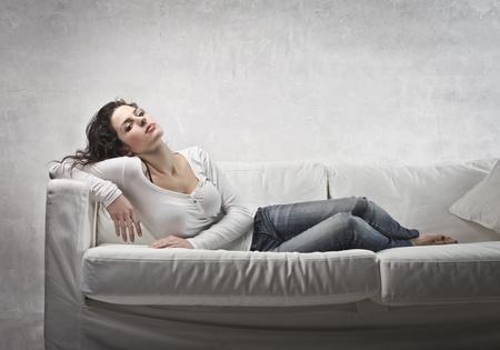 white sofa: Beautiful woman relaxing on a sofa
