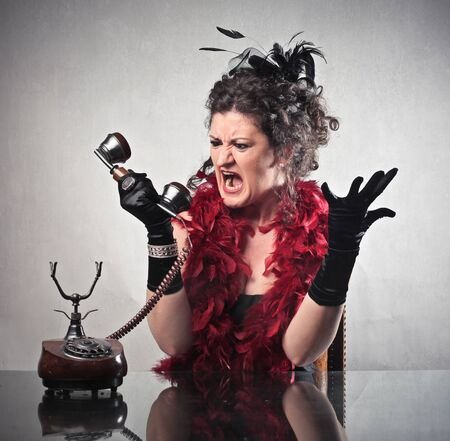 Angry elegant woman quarreling on the telephone photo