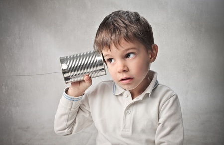 a communication: Child using a can as telephone Stock Photo