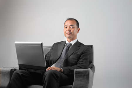 Japanese businessman sitting on an armchair and using a laptop photo