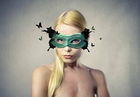Beautiful woman wearing a mask with the form of a butterfly photo