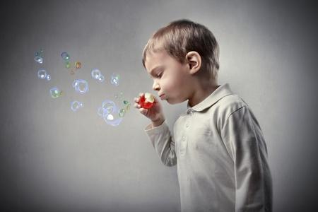 burbujas de jabon: Ni�o soplando pompas de jab�n Foto de archivo