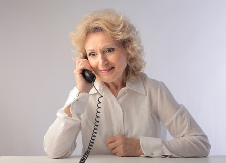 Smiling senior woman talking on the telephone photo
