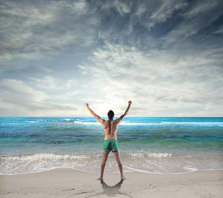 personas de espalda: El hombre estiramiento en frente del mar