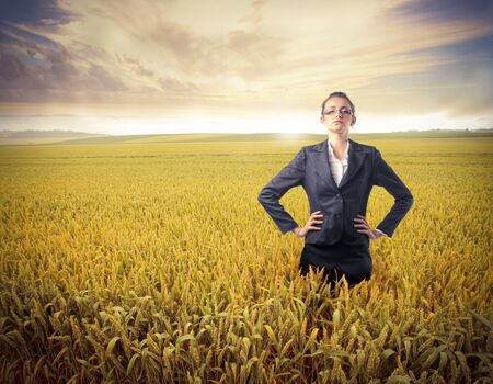 Businesswoman standing on a wheat field photo
