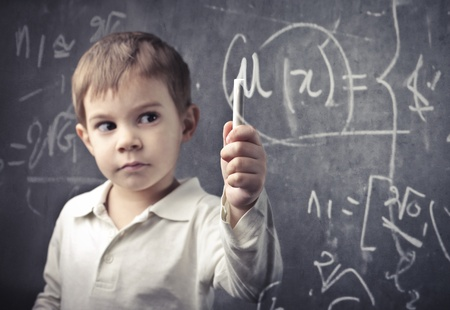 Child in a classroom holding a chalk photo