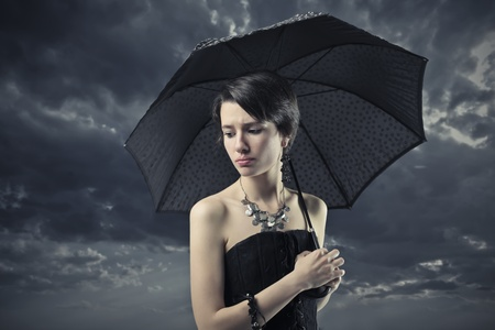 Sad elegant woman under an umbrella with stormy sky in the background photo