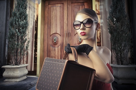 snob: Beautiful elegant woman in front of the entrance door of a luxury building Stock Photo