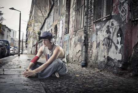 Young man sitting on a city street photo