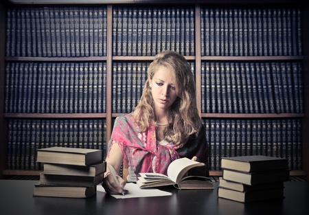 Woman in a library reading a book Stock Photo