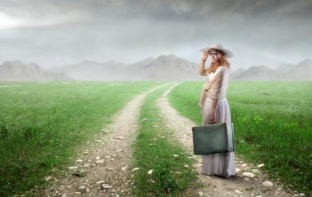 mujer con maleta: Elegante mujer llevando una maleta en una carretera de campo