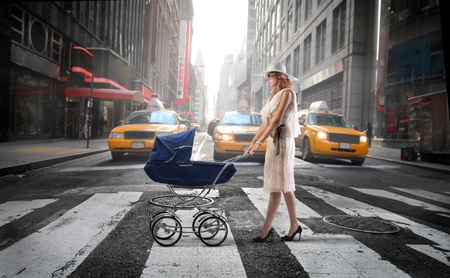 sitter: Mother crossing a city street with a pram