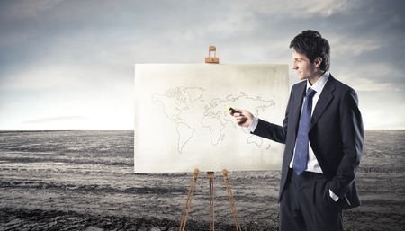 human geography: Businessman presenting a board with a planisphere