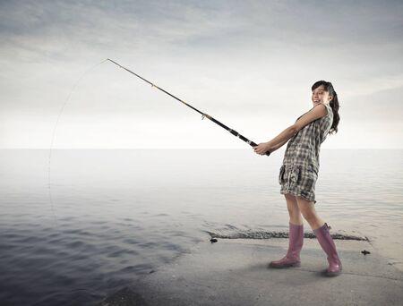 fishing rod: Smiling woman fishing on a pier