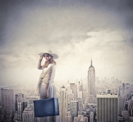 Beautiful woman carrying a suitcase with New York city in the background photo