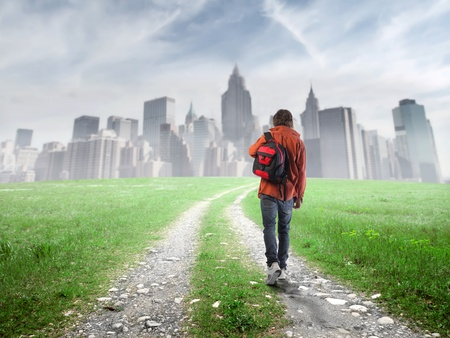 back roads: Student walking towards a city Stock Photo