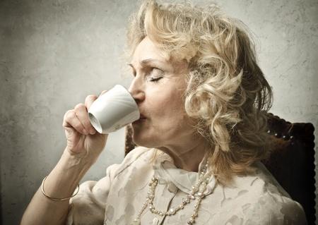 donna ricca: Senior donna bevendo una tazza di caffè