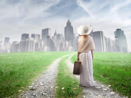 mujer con maleta: Bella mujer caminando hacia una gran ciudad una maleta en la mano Foto de archivo