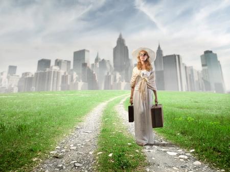 lejos: Hermosa mujer alejarse de una ciudad con un poco de equipaje