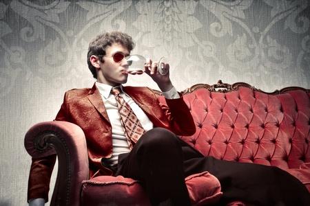 金持ち: 若い男はソファに座って、ワインのガラスを飲む