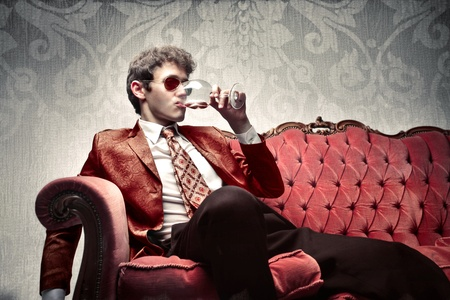 rich people: Young man sitting on a sofa and drinking a glass of wine