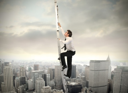energy work: Businessman clombing up a ladder with cityscape in the background Stock Photo