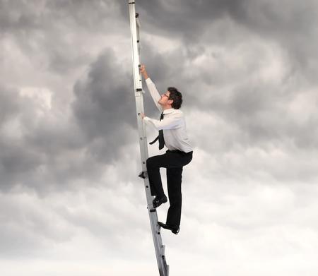 climbing ladder: Businessman climbing up a ladder  Stock Photo